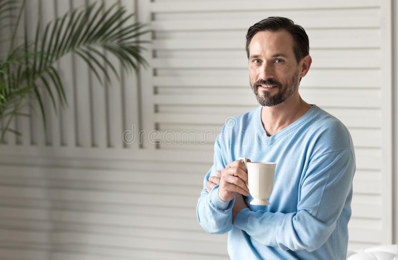 Radosny optymistycznie mężczyzna trzyma herbacianą filiżankę fotografia royalty free