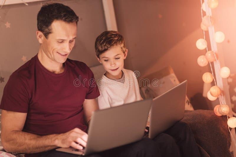 Radosny pozytywny ojciec i syn używa ich laptopy zdjęcia stock
