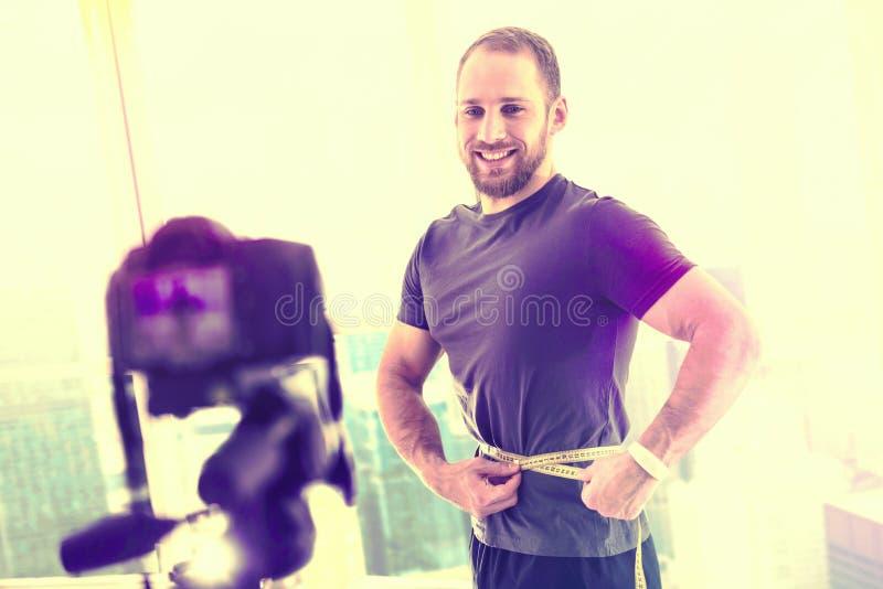 Radosny przystojny mężczyzna ono mierzy przed kamerą obrazy royalty free