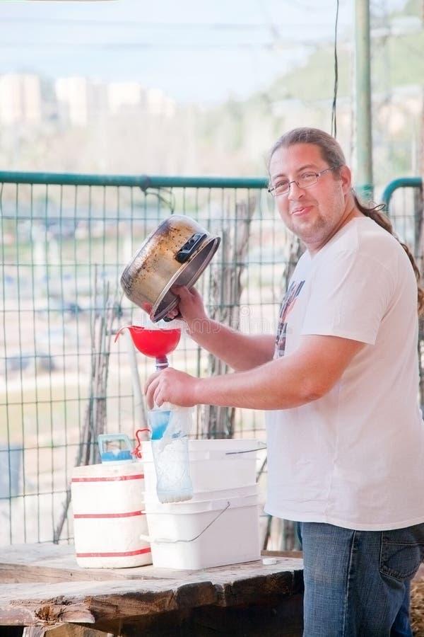 Radosny rolnik filtruje mleko obraz stock