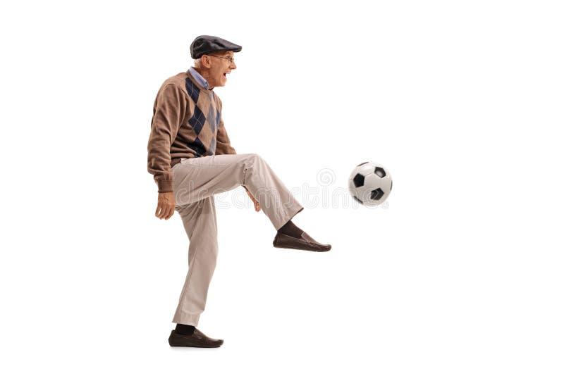 Radosny starszy mężczyzna kopie futbol obrazy stock