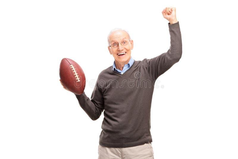 Radosny starszy mężczyzna trzyma futbol amerykańskiego zdjęcia royalty free