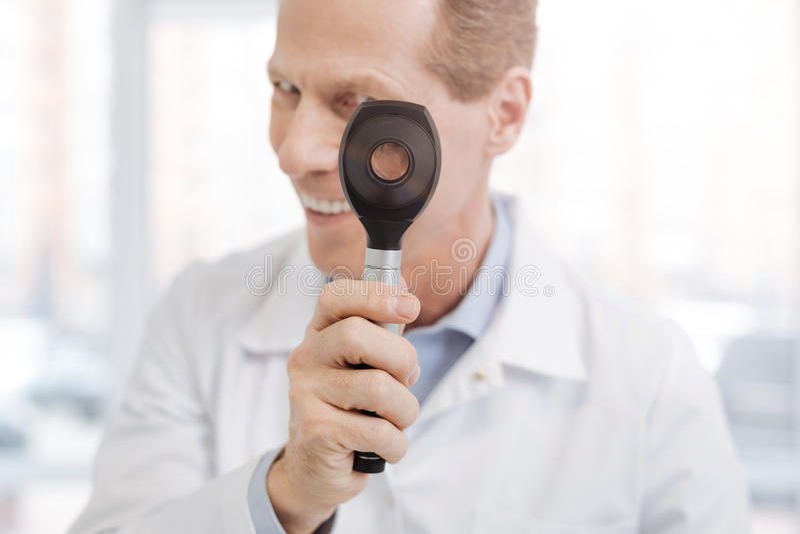 Radosny starzejący się doktorski mienia dermatoscope w gabinecie zdjęcie royalty free