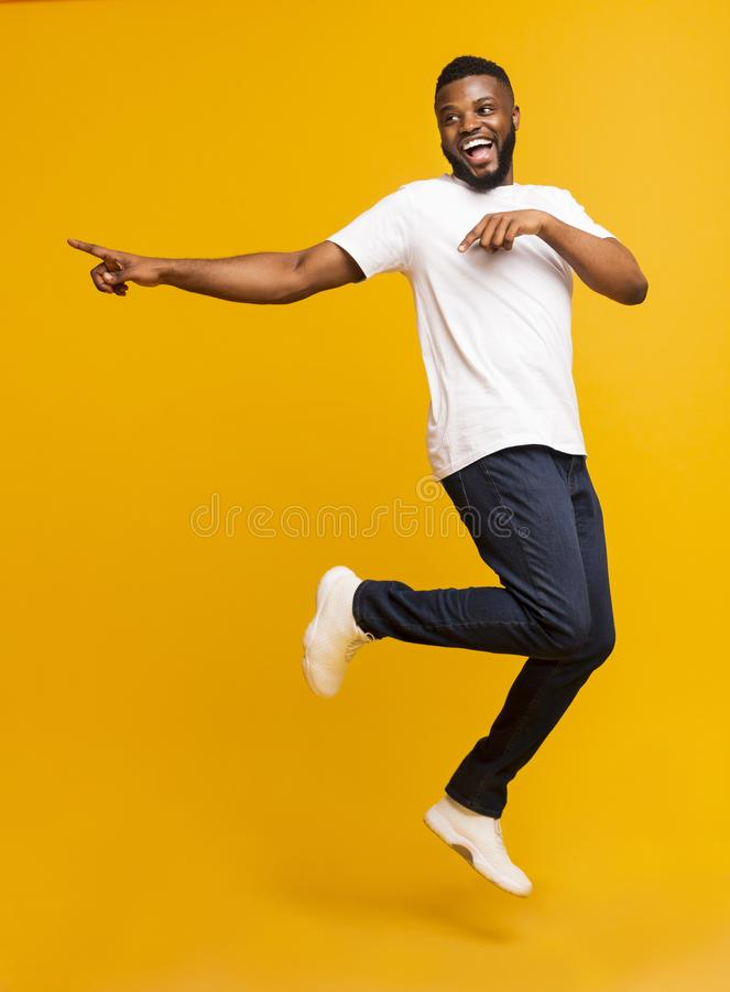 Radosny, tysiącletni facet skaczący w powietrze i wskazujący na bok zdjęcie stock
