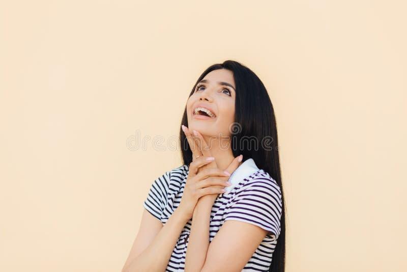Radosny wspaniały młody kobieta model patrzeje szczęśliwie upwards i utrzymanie ręka pod podbródkiem, zauważa coś przyjemnego, ub fotografia stock