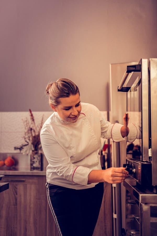 Radosny zadowolony kobieta kucharz cieszy się jej pracę obraz royalty free