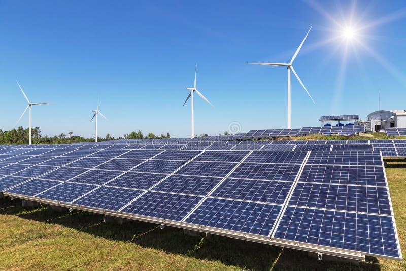 Radsamling av polycrystalline silikonsolpaneler och vindturbiner som frambringar elektricitet i hybrid- kraftverksystemstation arkivfoton