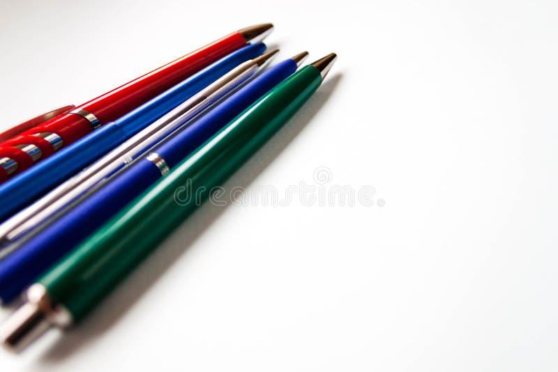 Radval av blandade mång- kulöra kulspetspennor av olika färger på ljust - blå bakgrund Tillbaka till skolakreativitet royaltyfri bild