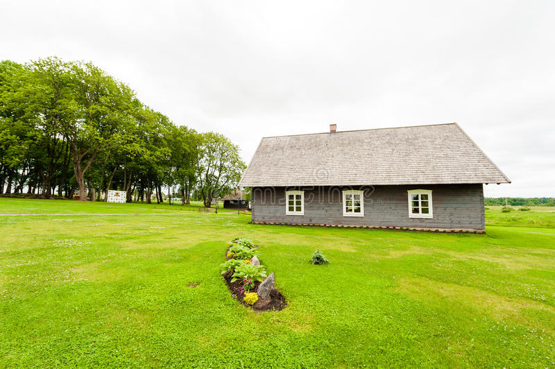 RADVILISKIS, LITHUANIA - JUNE 12, 2014: Unique Village and Rural Area in Lithuania with Wooden Building. Green grass and forest in stock photography