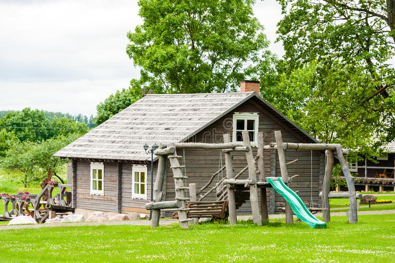 RADVILISKIS, LITHUANIA - JUNE 12, 2014: Unique Village and Rural Area in Lithuania with Wooden Building. Green grass and forest in royalty free stock photos