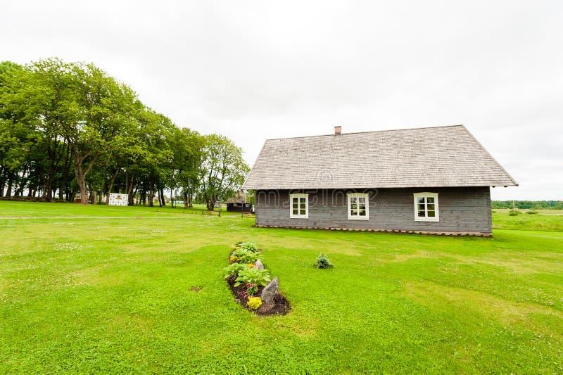 RADVILISKIS, LITUANIA - 12 DE JUNIO DE 2014: Pueblo único y zona rural en Lituania con el edificio de madera Hierba verde y bosqu fotografía de archivo