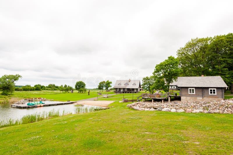 RADVILISKIS, LITUANIA - 12 DE JUNIO DE 2014: Pueblo único y zona rural en Lituania con el edificio de madera Hierba verde y bosqu imagen de archivo libre de regalías