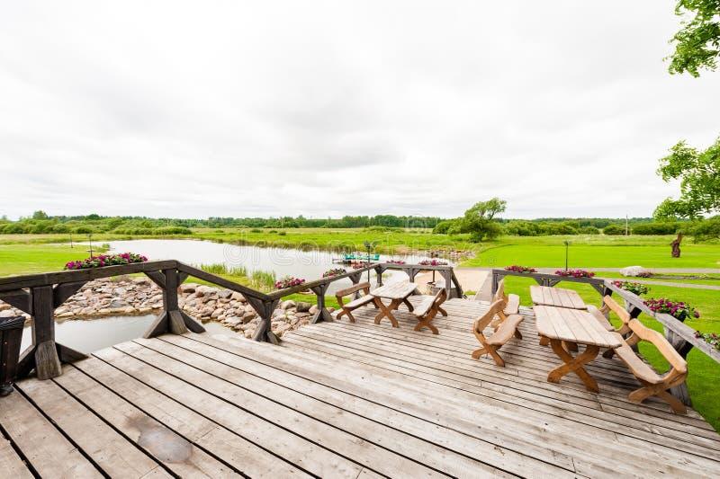 RADVILISKIS, LITUANIA - 12 DE JUNIO DE 2014: Pueblo único y zona rural en Lituania con el edificio de madera Hierba verde y lago  imágenes de archivo libres de regalías