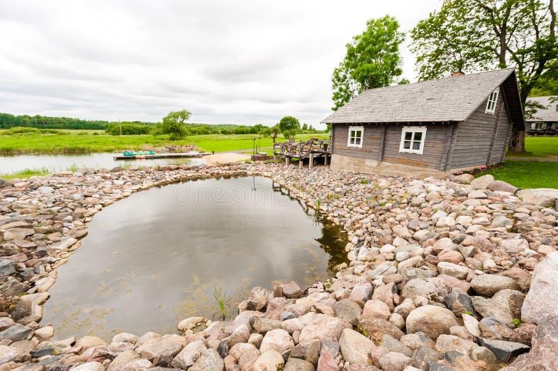 RADVILISKIS, LITUANIA - 12 DE JUNIO DE 2014: Pueblo único y zona rural en Lituania con el edificio de madera Hierba verde y lago  fotos de archivo