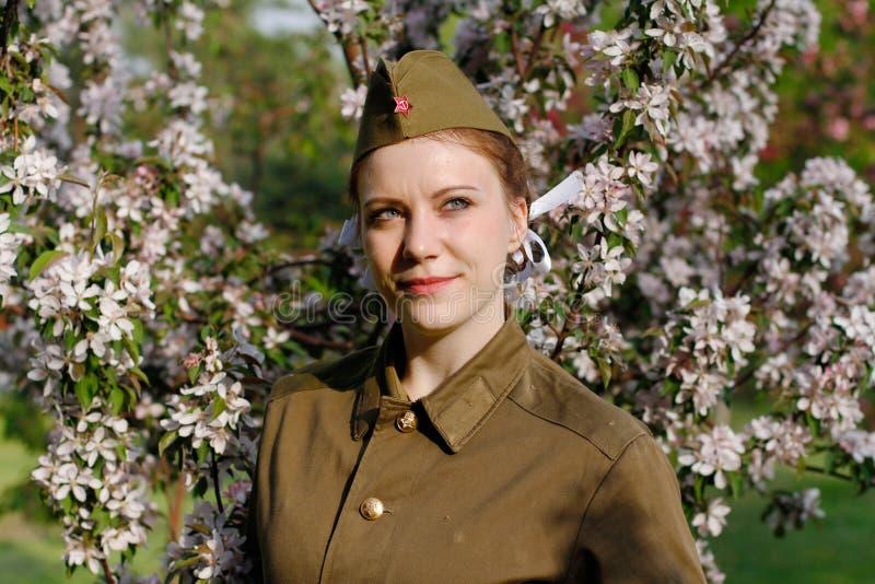 Radziecki żeński żołnierz w mundurze druga wojna światowa stoi blisko kwiatonośnego drzewa zdjęcia royalty free