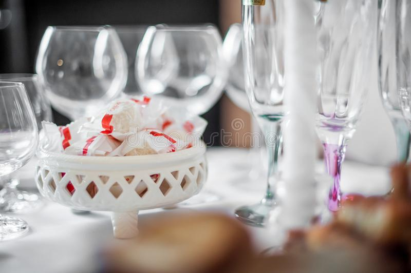 VILNIUS, LITHUANIA - JULY 07, 2012: Raffaelo Sweets on the table with empty glass of wine. Raffaelo Sweets on the table with empty glass of wine stock photography