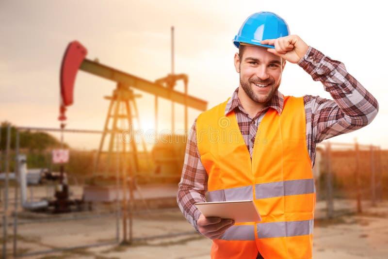 Raffinaderiarbetare med den digitala minnestavlan royaltyfri foto