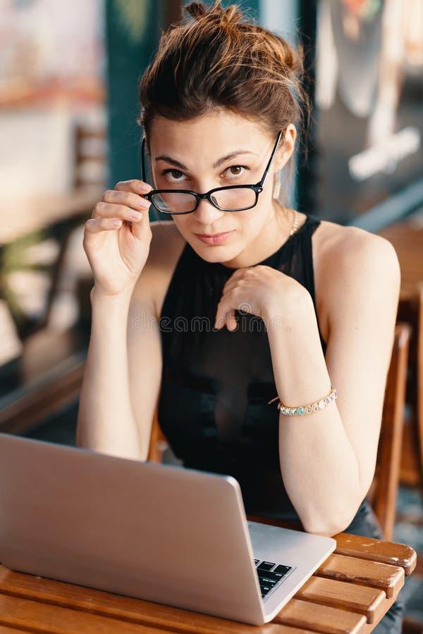 Raffinerad affärskvinna som ser över exponeringsglas som in sitter på tabellen royaltyfri fotografi