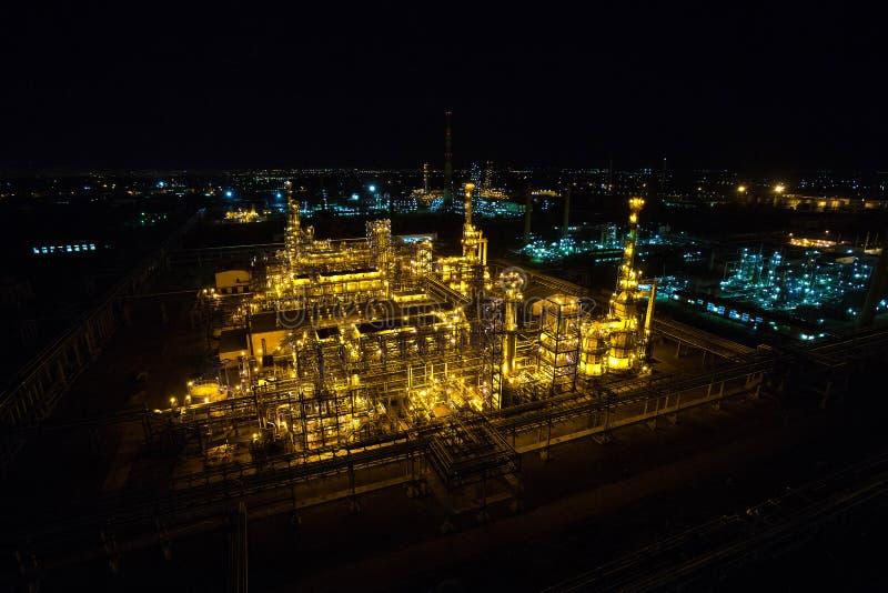 Raffineria di petrolio a penombra con i tubi e le costruzioni fotografia stock libera da diritti