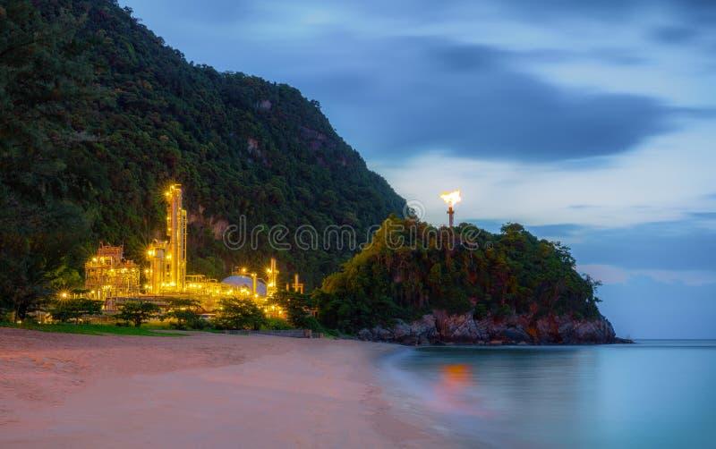 Raffinerieanlage mit Rauche und Feuer durch Meer auf Strand lizenzfreie stockfotografie