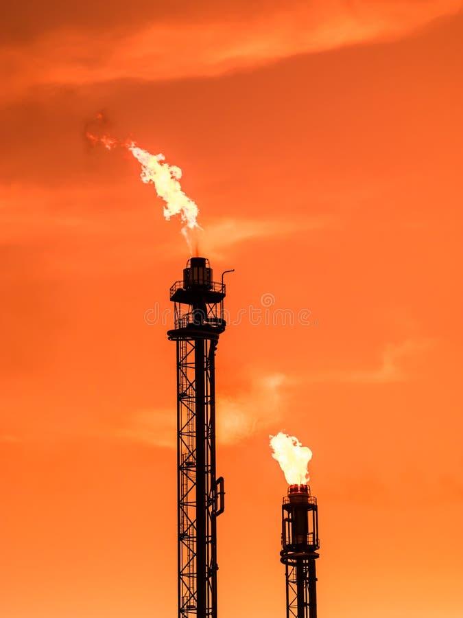 Raffineriekamin mit Feuer bei orange Sonnenuntergang stockfoto