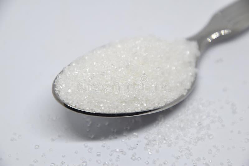 Raffinierter Zucker auf einem silbernen Teelöffel auf weißem Hintergrund lizenzfreie stockbilder