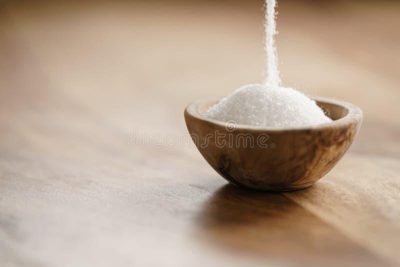 Raffinierter Zucker, der in hölzerne Schüssel auf Tabelle fällt stockfotos
