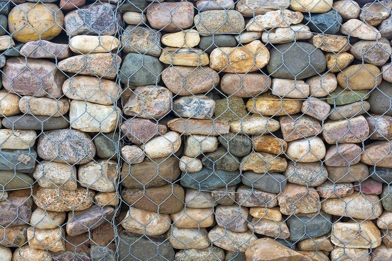 Rafforzamento della costa di Stonework Chiudi Sfondo astratto Le pietre delle reti di ferro proteggono la spiaggia e la costa dal immagini stock