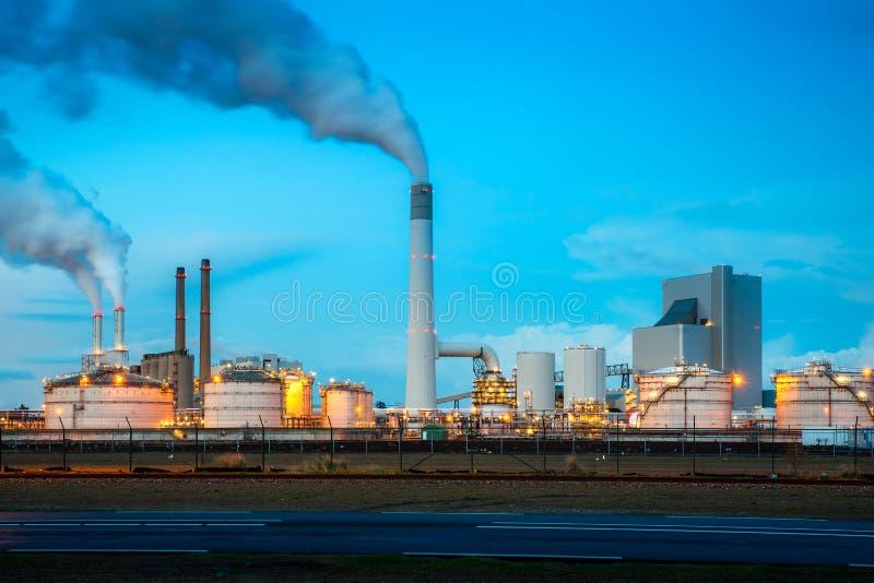 Rafineria ropy naftowej przemys? przy noc? w Rotterdam, holandie Zanieczyszczenie dym od rafineria ropy naftowej przemysłu używa  fotografia royalty free