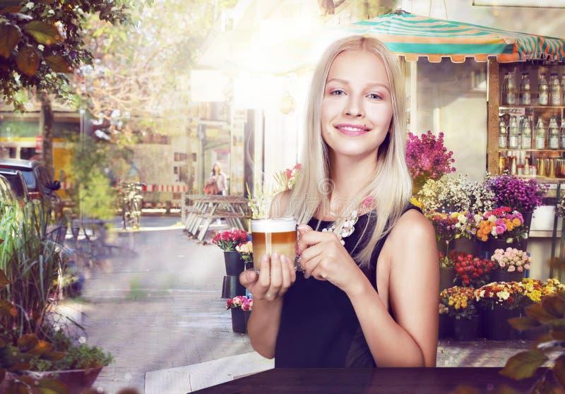 rafraîchissement Femme heureuse avec la tasse de café dans un café de rue photos stock
