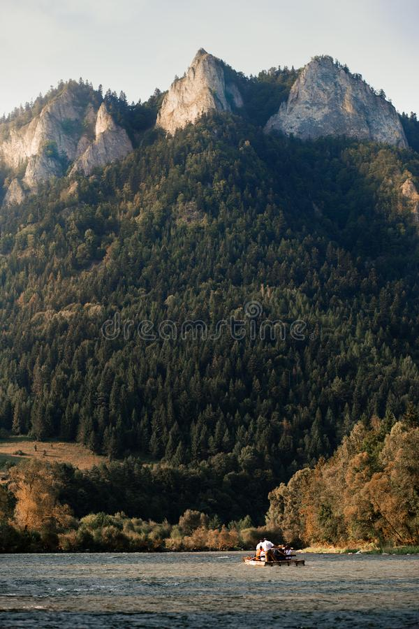 Raft ride on The Dunajec river at the foot of Pieniny Mountains. Group of people enjoying trip on raft going down the river. Trzy Korony Three Crowns peak over royalty free stock image