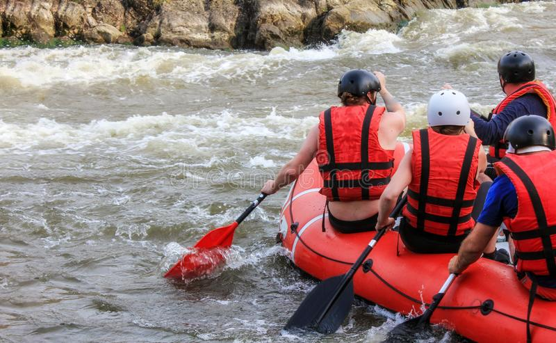 Rafting av laget, extrem vattensport f?r sommar Grupp m?nniskor i ett rafting fartyg, h?rlig adrenalinritt ner floden royaltyfri bild