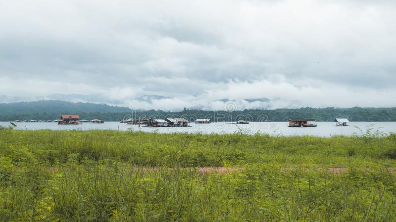 Rafting boats on Great view of Khao lam lake. Dramatic and picturesque scene. Foggy after rain over the lake and mountains.Popular stock photography