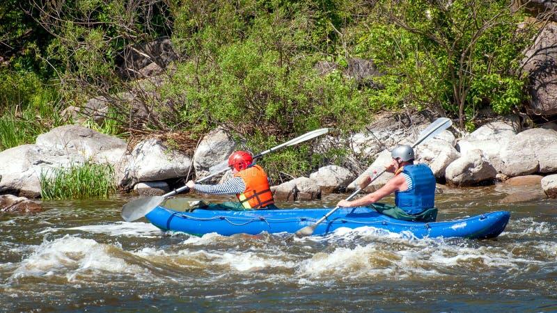 Rafting e kayak Due sportivi stanno navigando su una barca gonfiabile di gomma teamwork Turismo ecologico dell'acqua fotografia stock libera da diritti