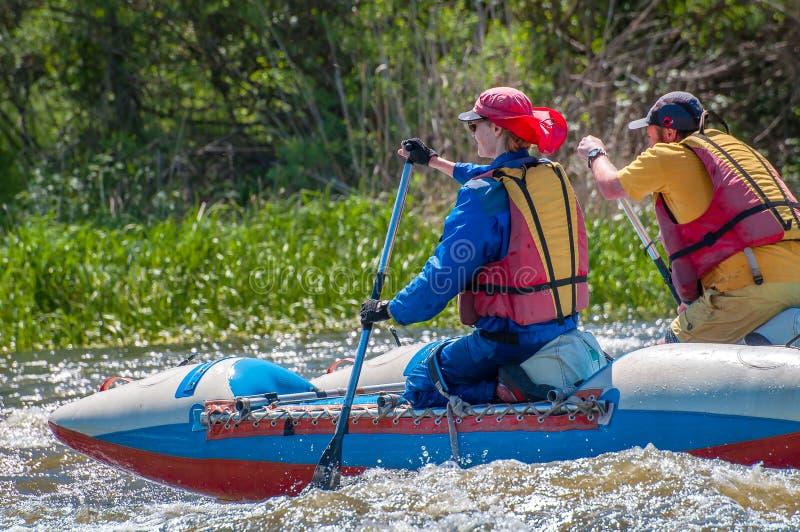 rafting Navegación casada jóvenes de la pareja en un barco inflable de goma en una corriente tempestuosa del agua El agua salpica foto de archivo