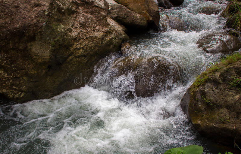 Rafting river among black rocks. Fresh water fast stream in stones. royalty free stock photos