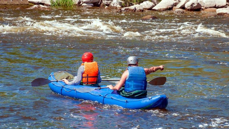 Rafting som kayaking Två idrottsman nen i sportutrustning seglar på ett rubber uppblåsbart fartyg Teamwork royaltyfria bilder