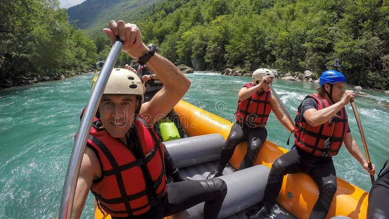 Group Of Men And Women Rafting On White Water. Rafting team on white water. Active vacations, team concept. A group of people enjoying white water rafting stock images