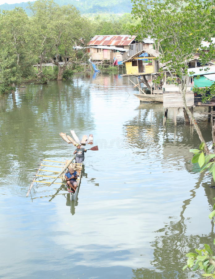 Rafting wood. Woman paddling small traditional wooden boat with wood behind and man smoking on the river with poor houses and trees on bank (Sorong, Papua stock photos