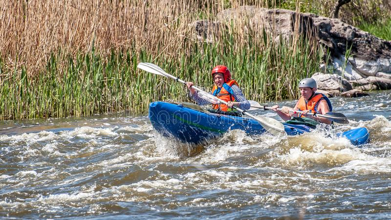 Rafting. Young married couple sailing on a rubber inflatable boat in a stormy stream of water. Water splashes close-up. Myhiya, Ukraine - May 1, 2018: Rafting royalty free stock photography