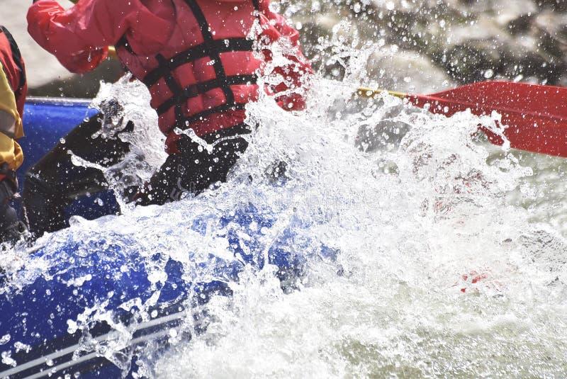 Raftingsteam die de golven bespatten, die uiterste rafting stock afbeeldingen