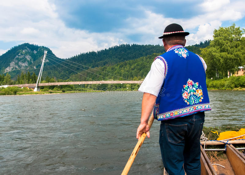 Raftsman rafts tourists on the Dunajec river, south of Poland. T. DUNAJEC RIVER, POLAND - JUNE 26, 2015: Raftsman rafts tourists on the Dunajec river, south of royalty free stock photos