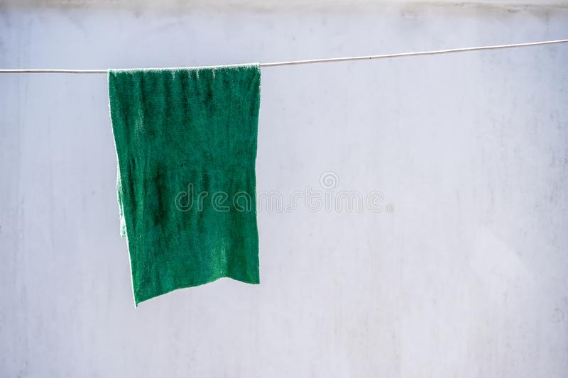 Rag on the clothesline. With wall background stock photos