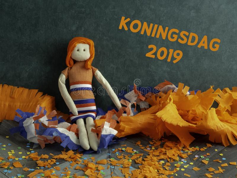 Rag doll sitting amidst Kings dag & x28;Koningsdag in Dutch& x29; decorations royalty free stock images