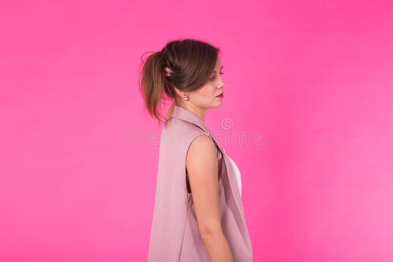 Ragazza abbastanza alla moda con capelli lunghi che posano contro il fondo rosa Ritratto di modo di giovane donna sorridente feli fotografia stock