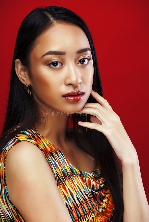 Ragazza abbastanza asiatica dei giovani con trucco che posa sul fondo rosso, diverso concetto della gente di rases di stile di vi fotografie stock libere da diritti