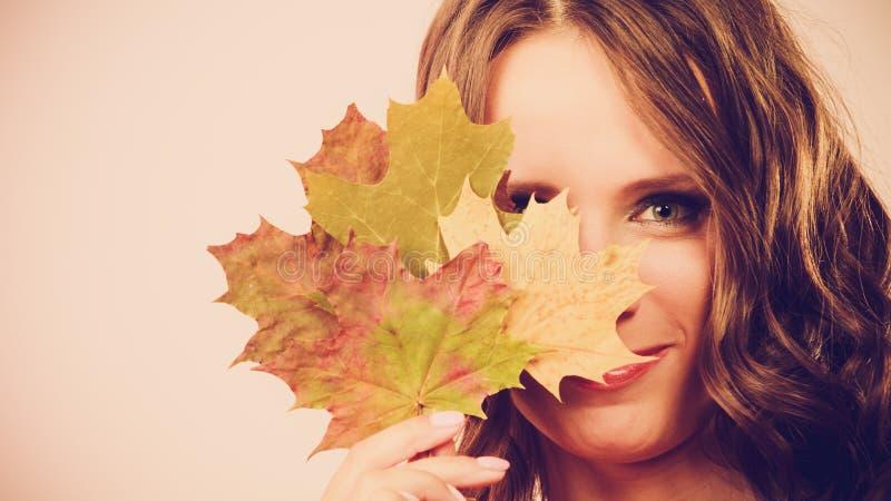 Ragazza abbastanza autunnale con le foglie di acero a disposizione immagini stock libere da diritti