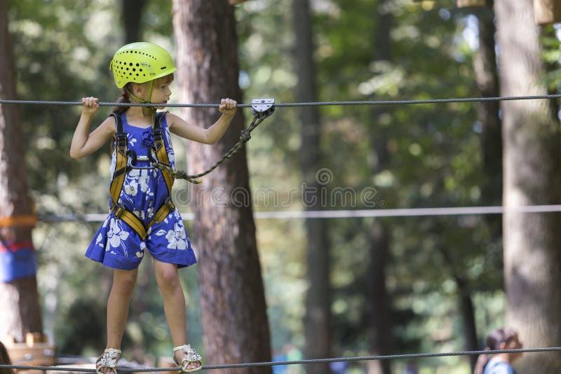 Ragazza abbastanza bionda del bambino dei giovani in cavo di sicurezza e casco sul ro immagine stock libera da diritti