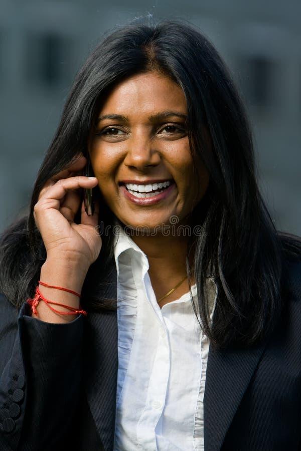 Ragazza abbastanza indiana che per mezzo del telefono mobile immagine stock libera da diritti