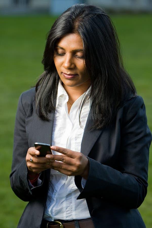 Ragazza abbastanza indiana che per mezzo del telefono mobile immagine stock